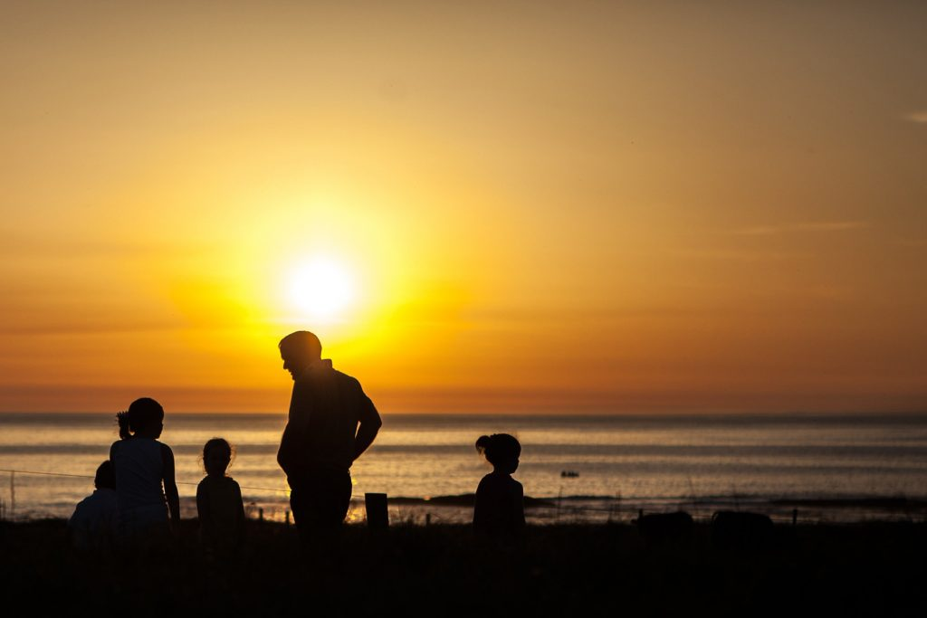 a family plays at the water during a sunset