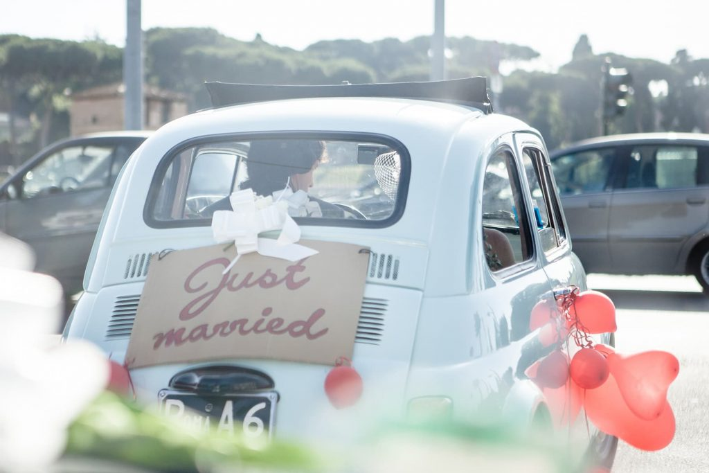 bride and groom drive away in traditional Italian Vespa with a just married sign on the back