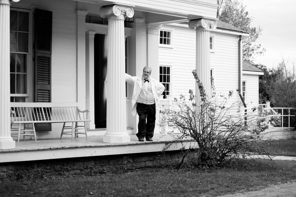 a man waits on the porch entrance of a home in the village