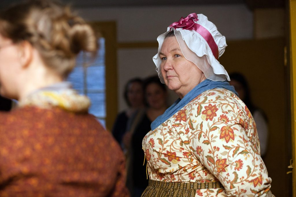a woman in traditional clothing at genesee country village museum
