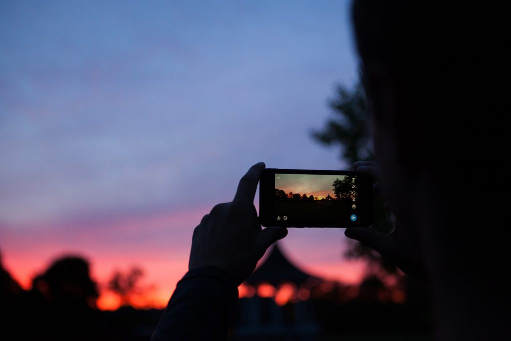 person takes a sunset picture through camera