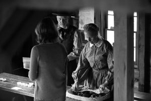woman dressed in 19th century clothing serves a tour at a museum