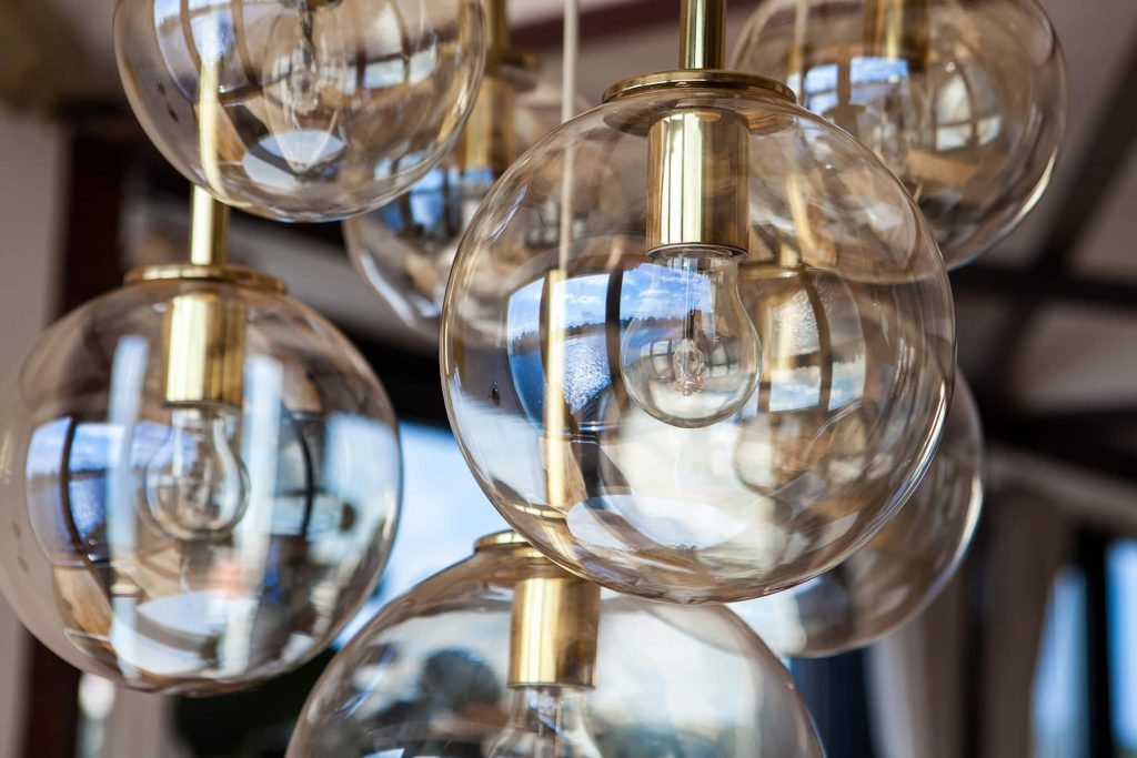 large glass globe lights hang from the ceiling with reflections