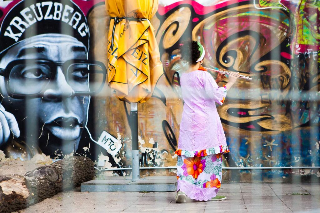a woman plays music and dances in the park in front of a large mural of a man