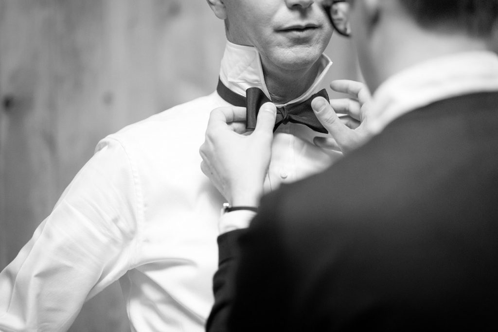 groom has his tie straightened by his best man before marrying his wife