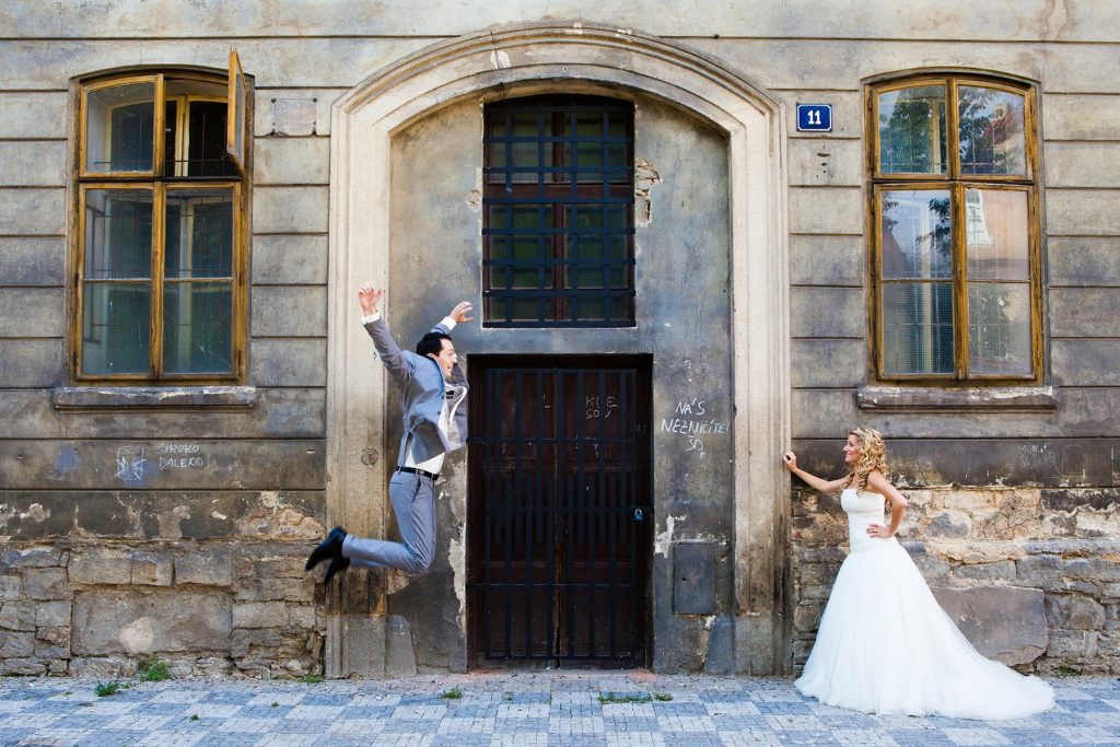 groom jumps for bride in front of a historic building