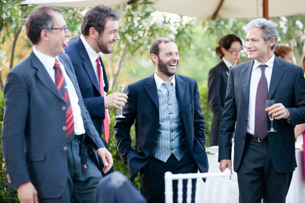 men laugh and tell stories while drinking champagne during cocktail hour
