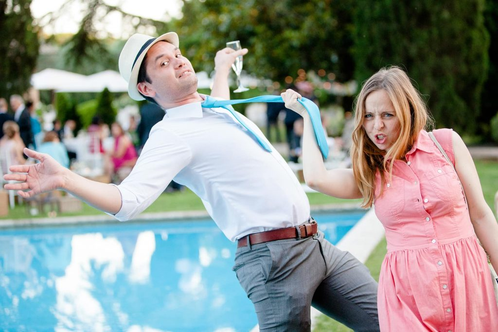 girlfriend holds boyfriend's tie during reception as he pretends to fall in the pool
