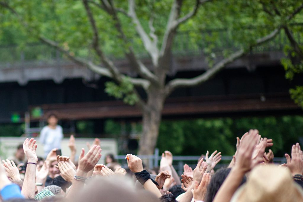 people throw their hands up to the music at an outdoor concert in the city