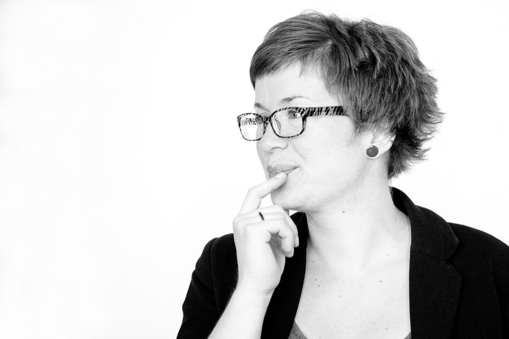 application photograph of woman in black and white wearing glasses