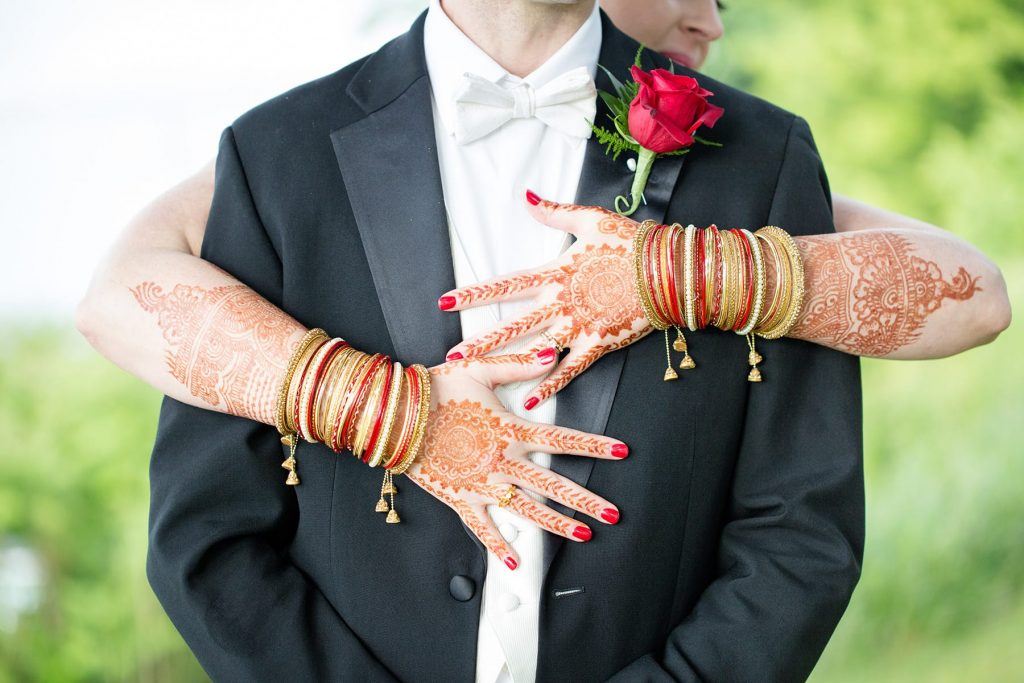 henna painted arms of a bride hug her husband after the ceremony