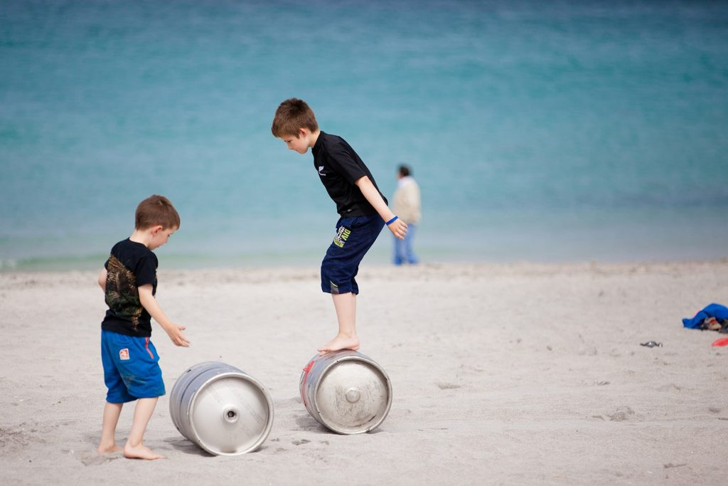 two boys balance on barrels on the beach and sand in front of the water