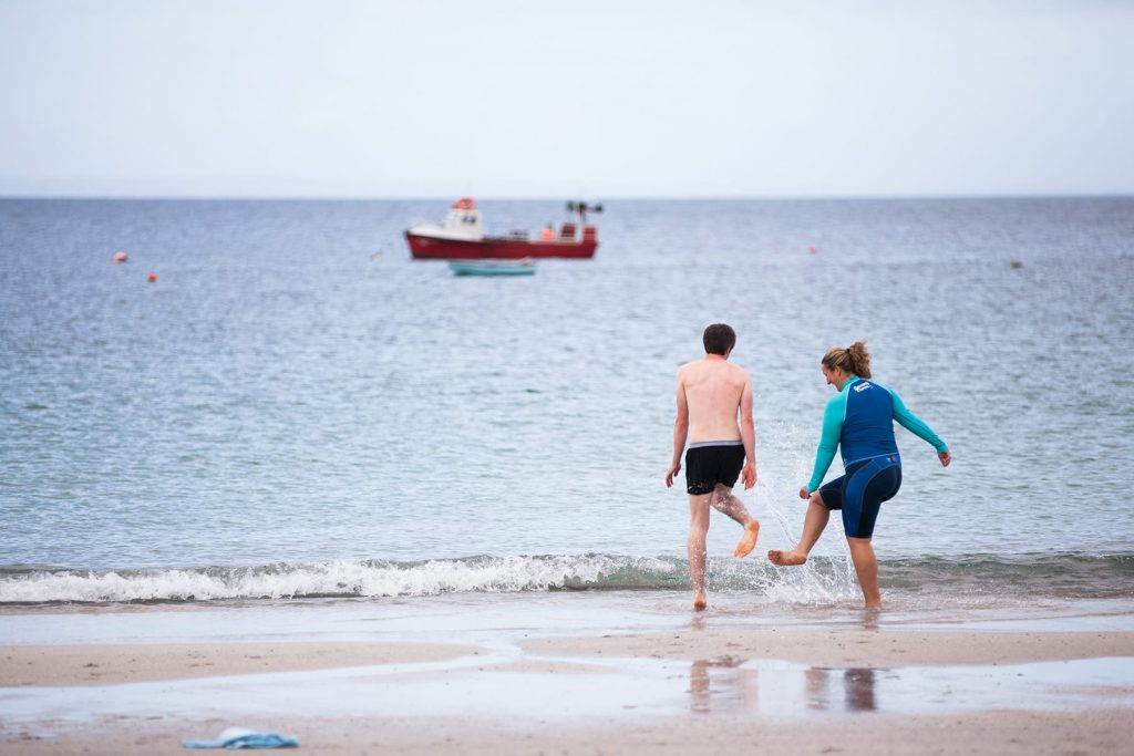a couple splashes in the cold water on the beach before going swimming