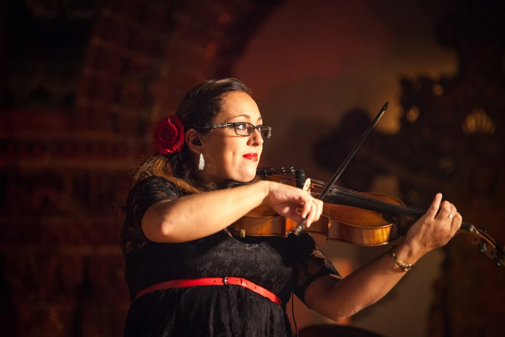 a violin player performs for her audience on stage