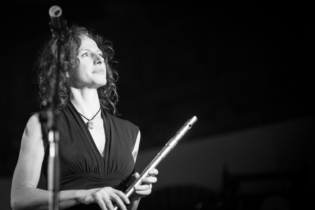 an Irish flute player looks at the lights while she is on stage