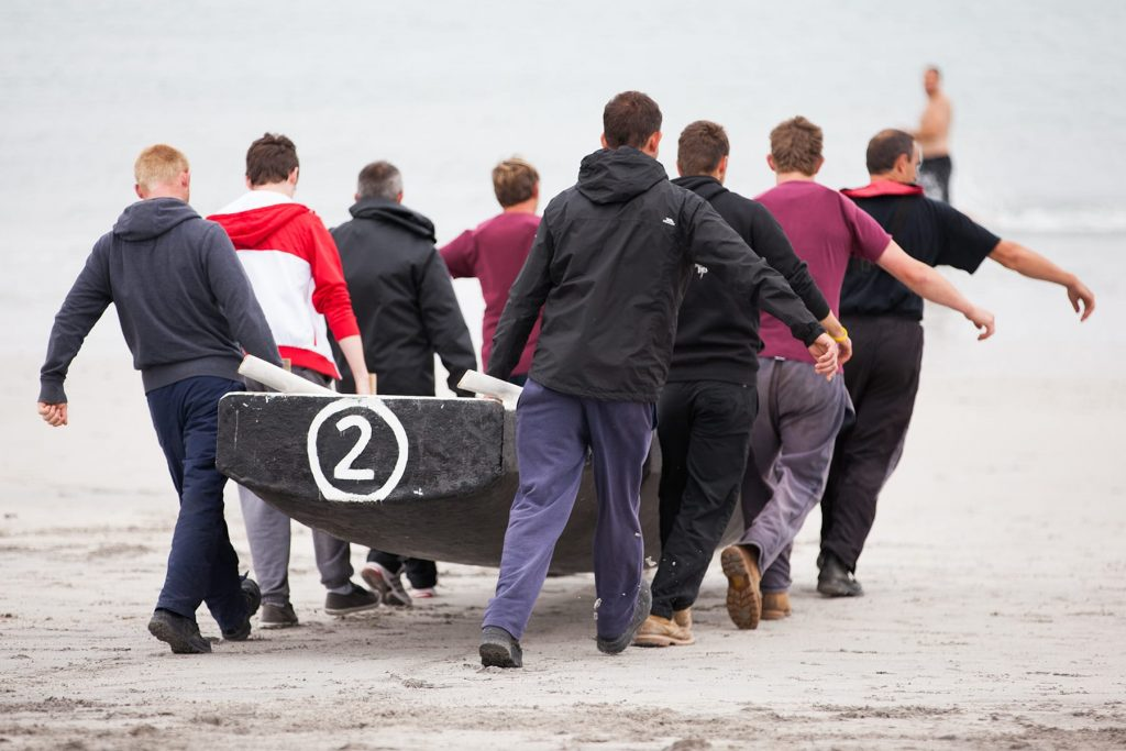 men on a team carry their Currach boat to the water before a race