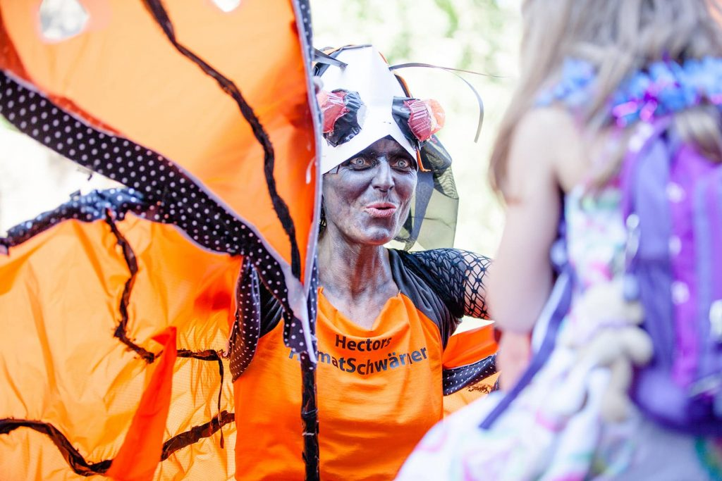 A monarch butterfly costume with wings and dramatic makeup at a cultural parade