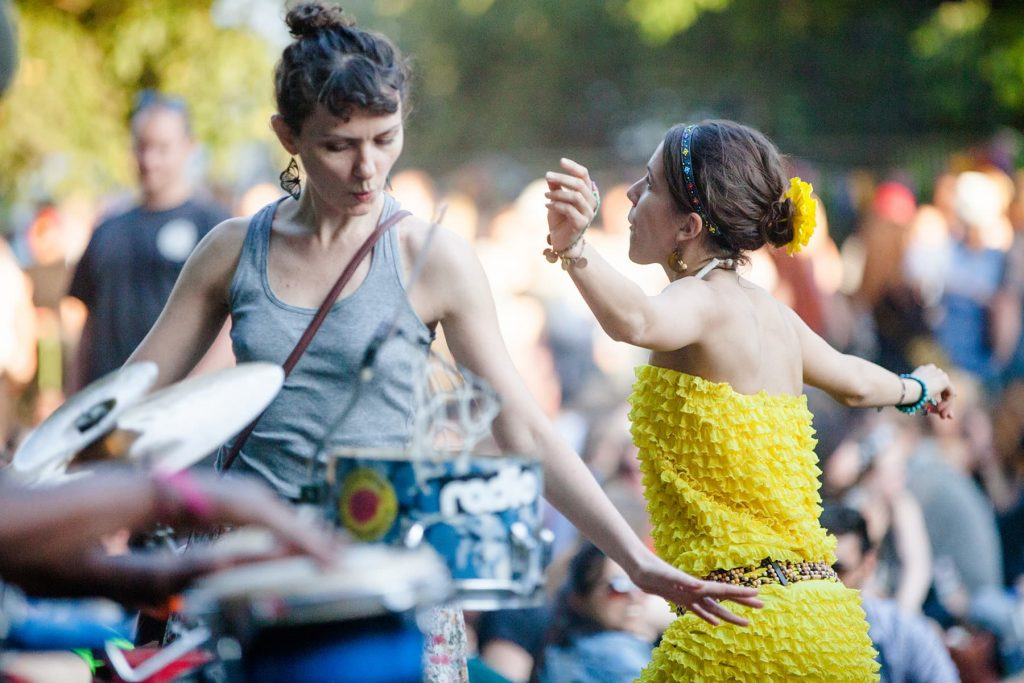 two women dance at a music festival in a park in the city