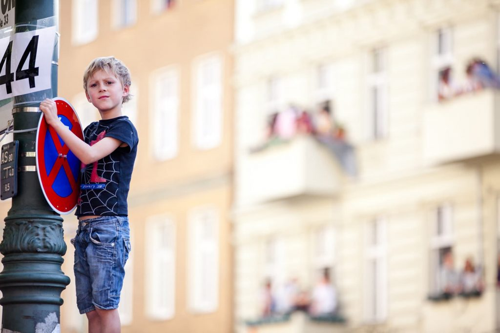 boy standing on a sign overlooking the parade from above