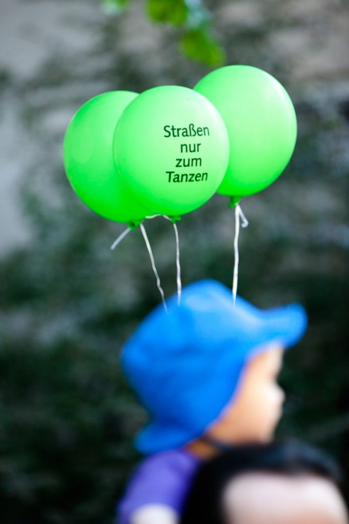 a boy in a parade holds 3 green balloons that say the street is only for dancing