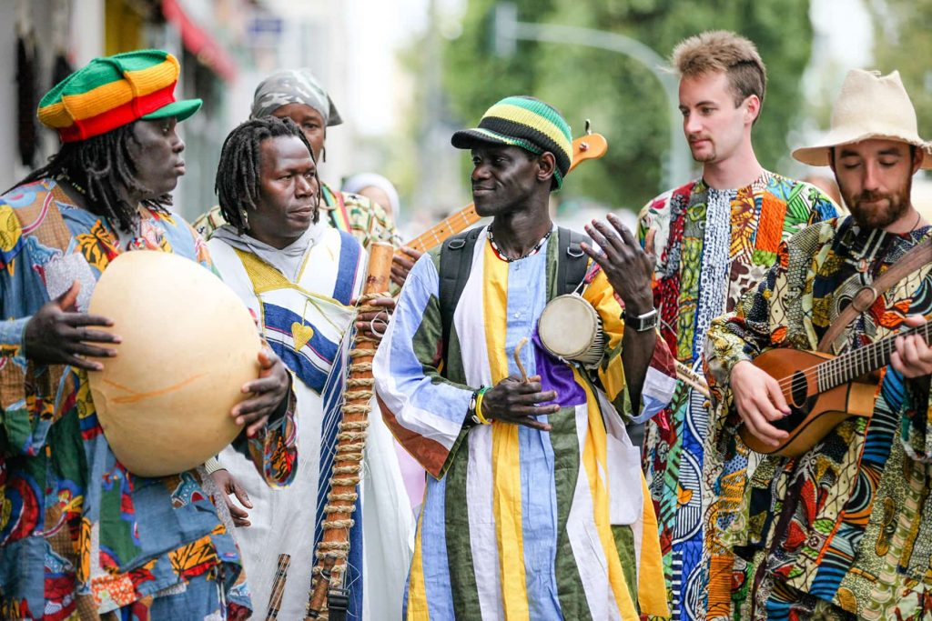 an African musical group walks through the streets while playing