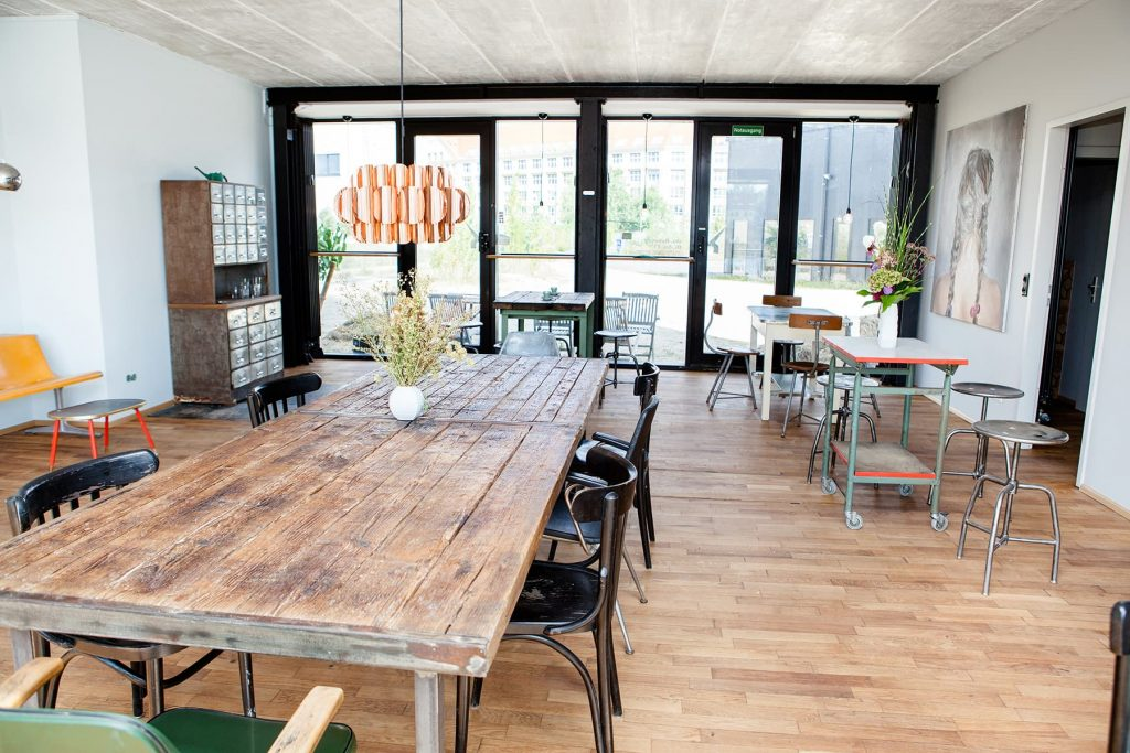 a hand-crafted table in a luxury building with a cafe on the ground floor