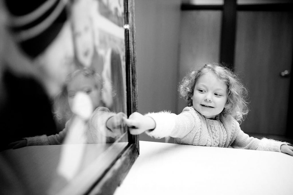 a little girl pointing to her family portrait