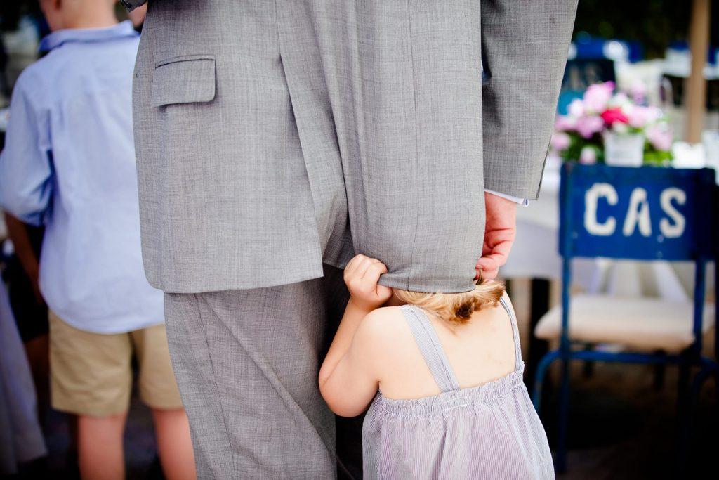 child hides underneath father during speeches