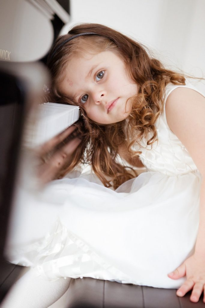 young girl in a wedding dress rests her head on the piano