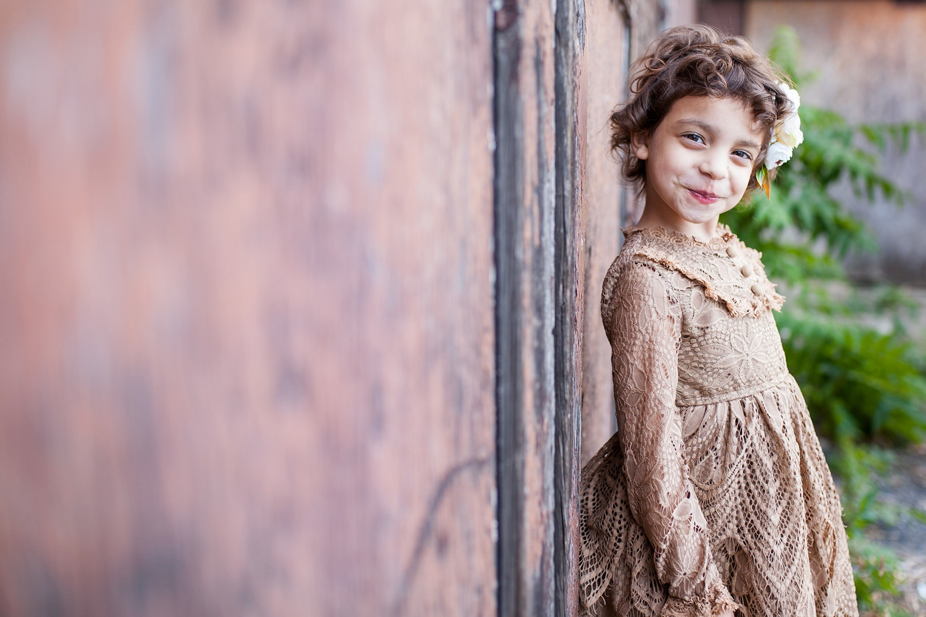 girl leaning against a rusty wall in a brown lace dress in Rochester NY