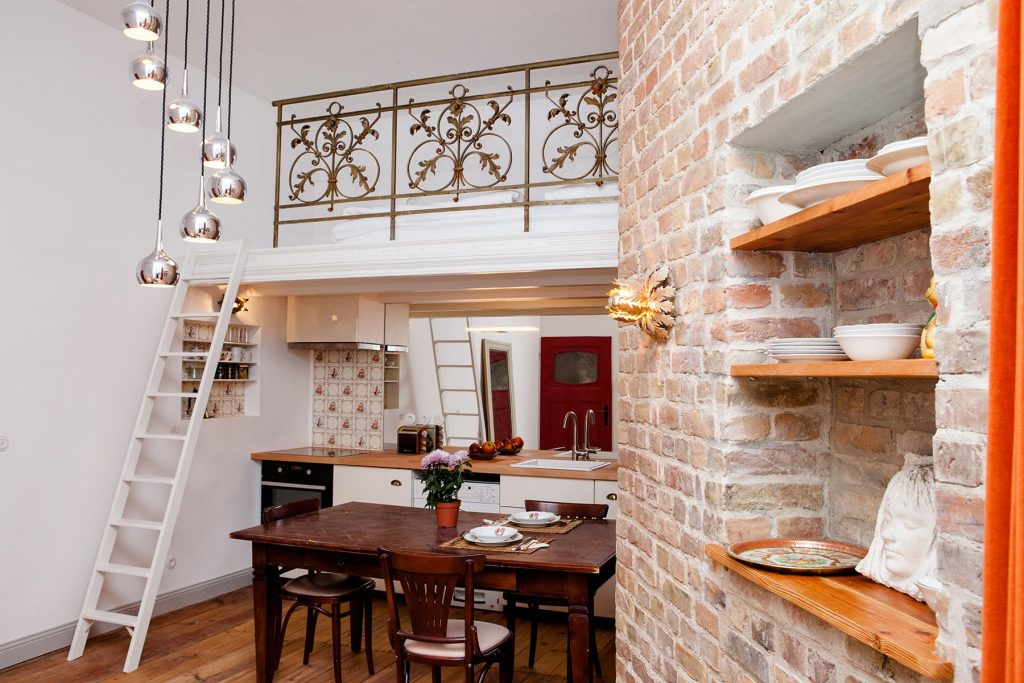 loft apartment with a ladder brick wall and iron railing