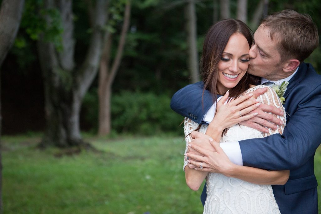 bride and groom embrace during their photoshoot in Webster along the water at the Lodge at Abraham Lincoln Park