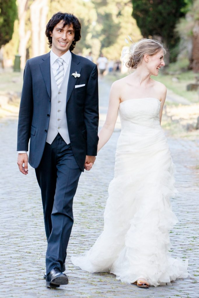 bride and groom laugh and hold hands while walking down the street during the shoot