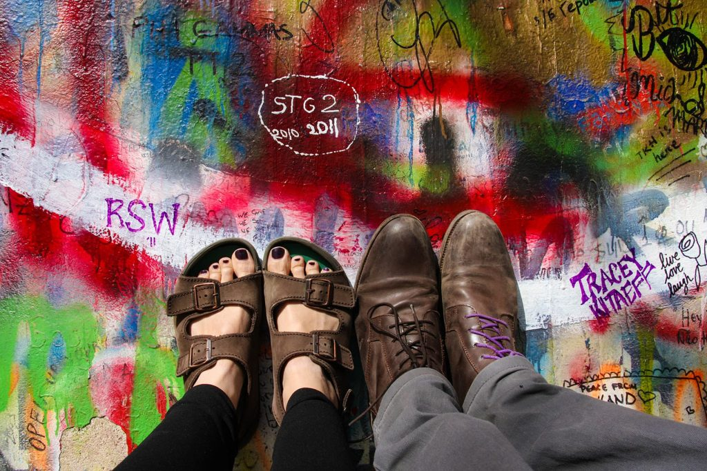 feet leaning against the John Lennon memorial wall