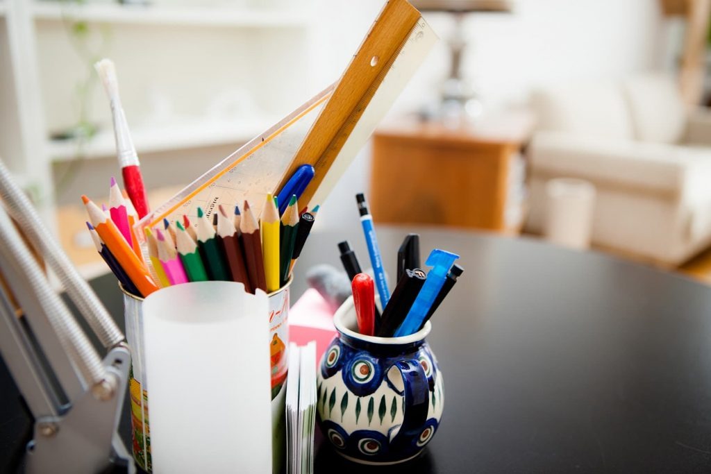 colored pencils and other drawing material on a desk