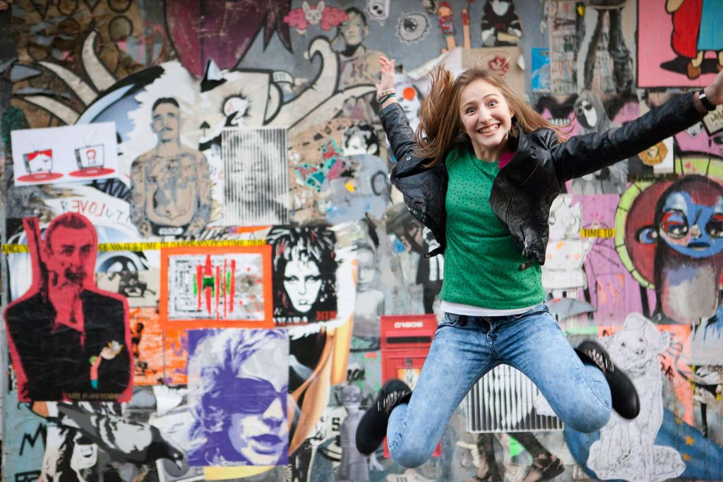 senior girl portrait jumping in front of a mural