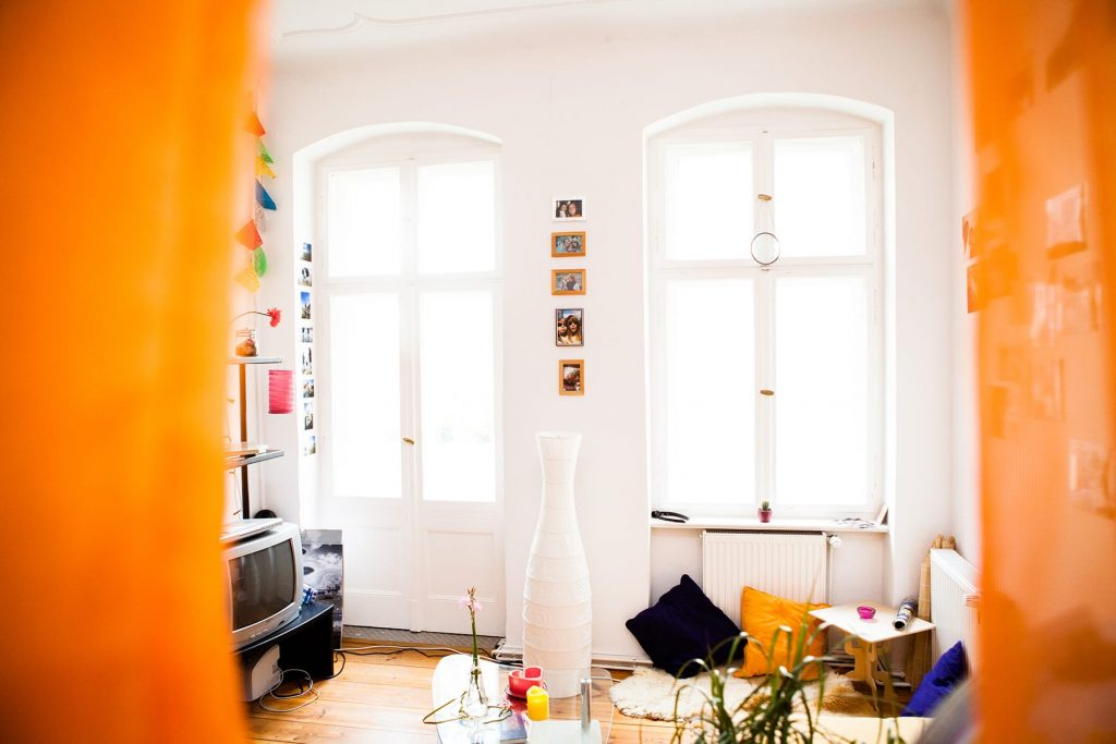 a room in a small apartment with orange curtains