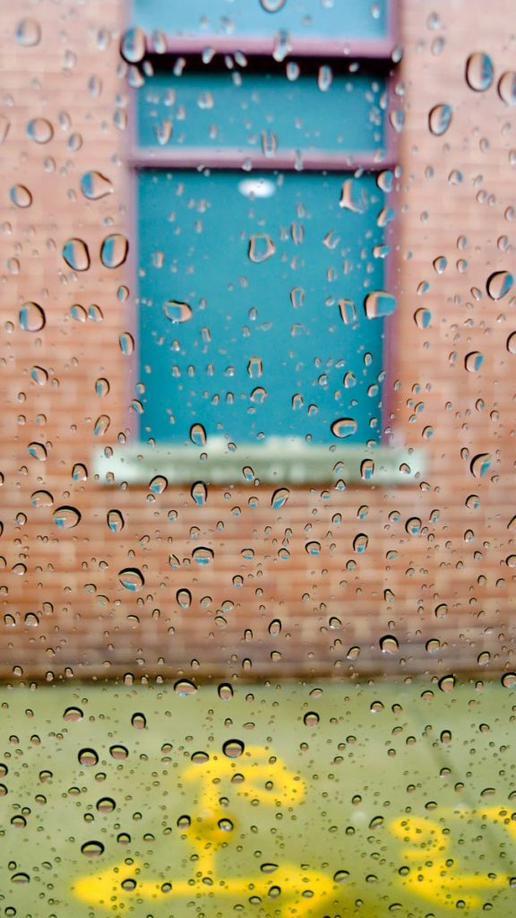 raindrops gather on a window of a car with colors in the background