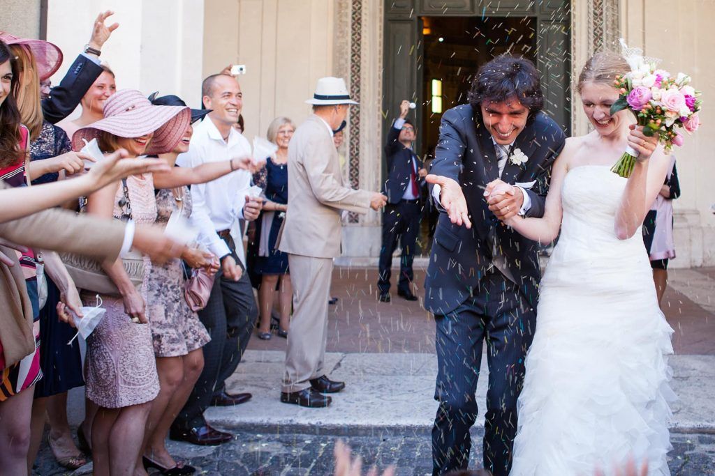 guests throw rice at bride and groom as they exit after the church