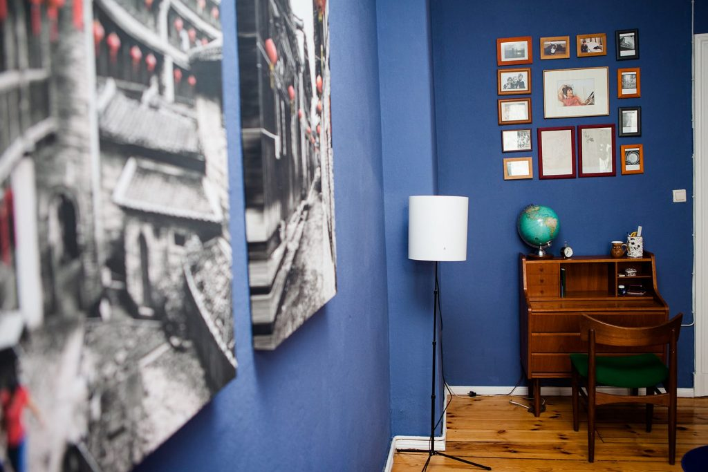 A room with blue walls and nicely organized pictures and photographs on the wall