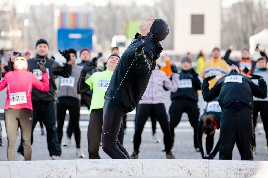 a coach warms up and stretches with the runners of the marathon