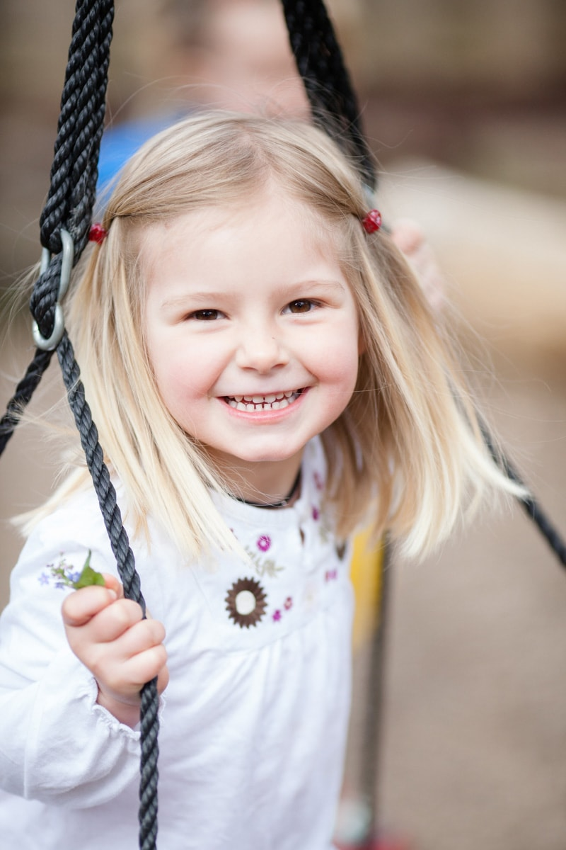 little girl happy on a swing