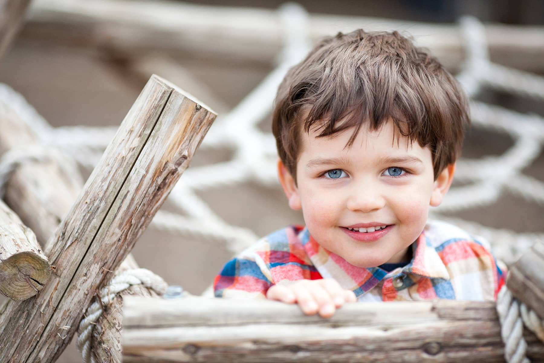 toddler-aged boy playing on jungle gym with blue eyes