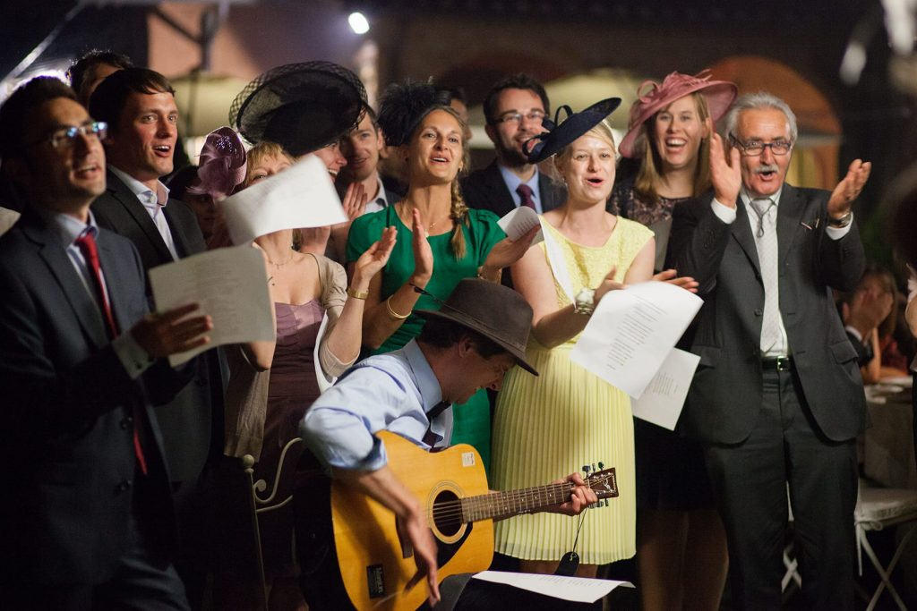 wedding party and family sing and serenade the bride and groom during the evening