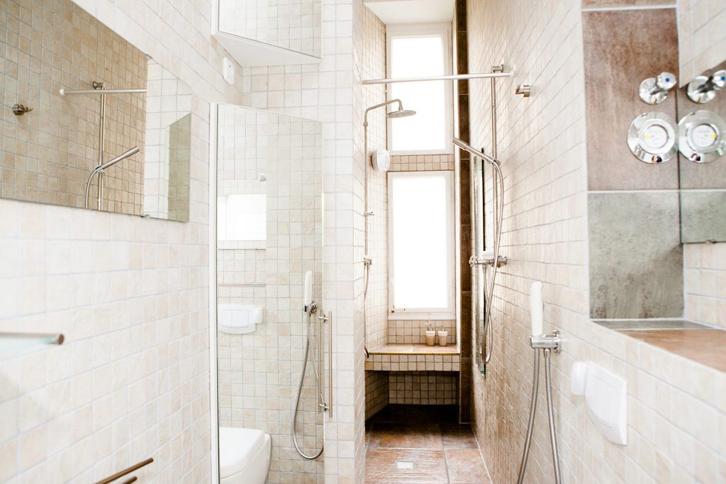 beautiful remodeled shower with tiles and excessive light coming in the windows