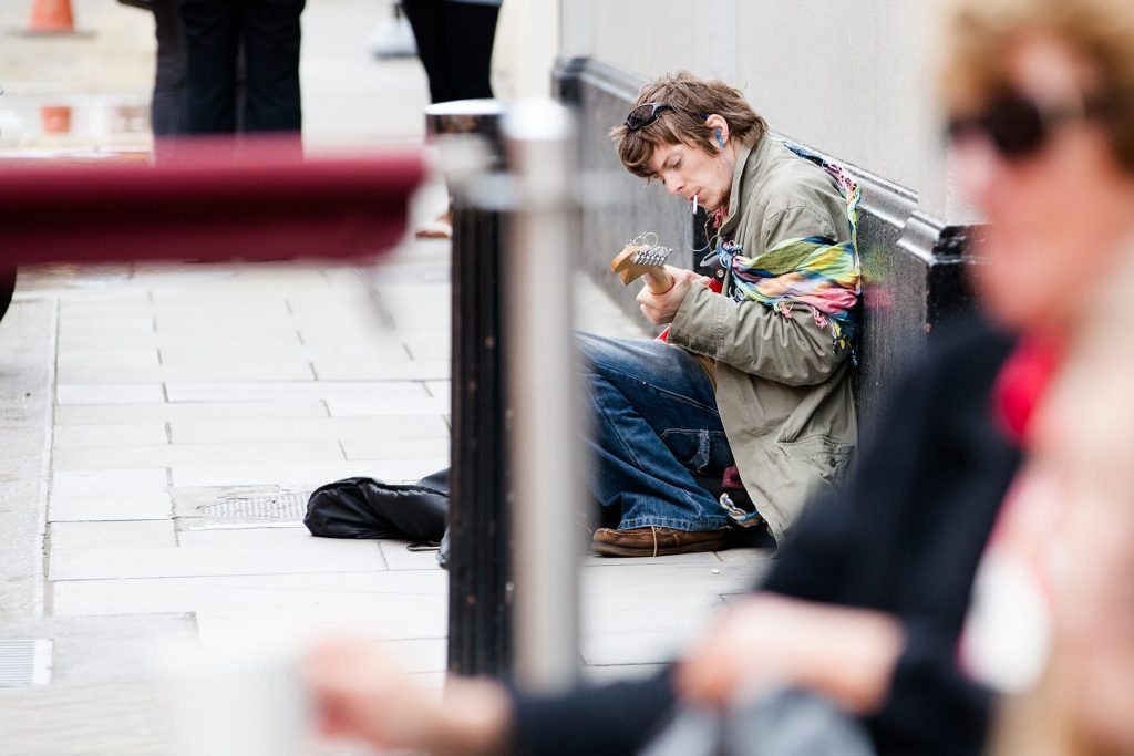 street musician busks outside while smoking a cigarette