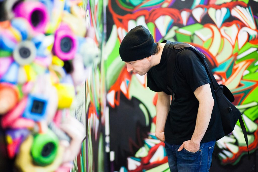 a man looks at a piece of giant mural with many colors and shapes