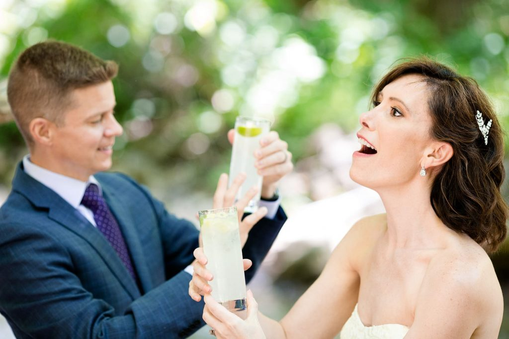 bride and groom celebrate after their ceremony with a glass of champagne