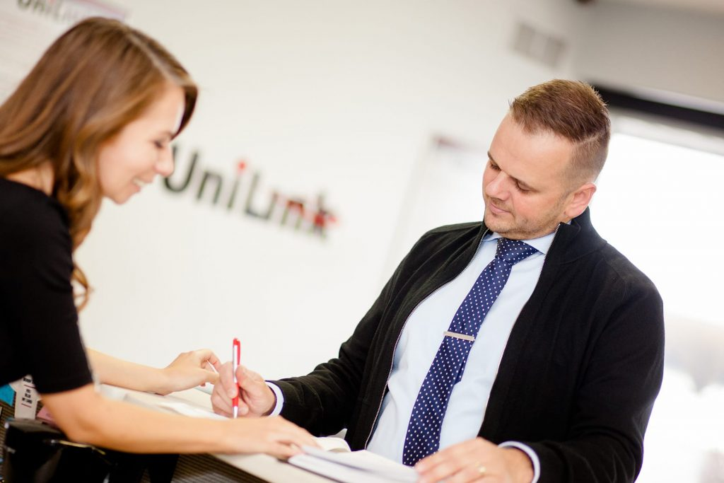 receptionist at UniLink in Rochester greets customer