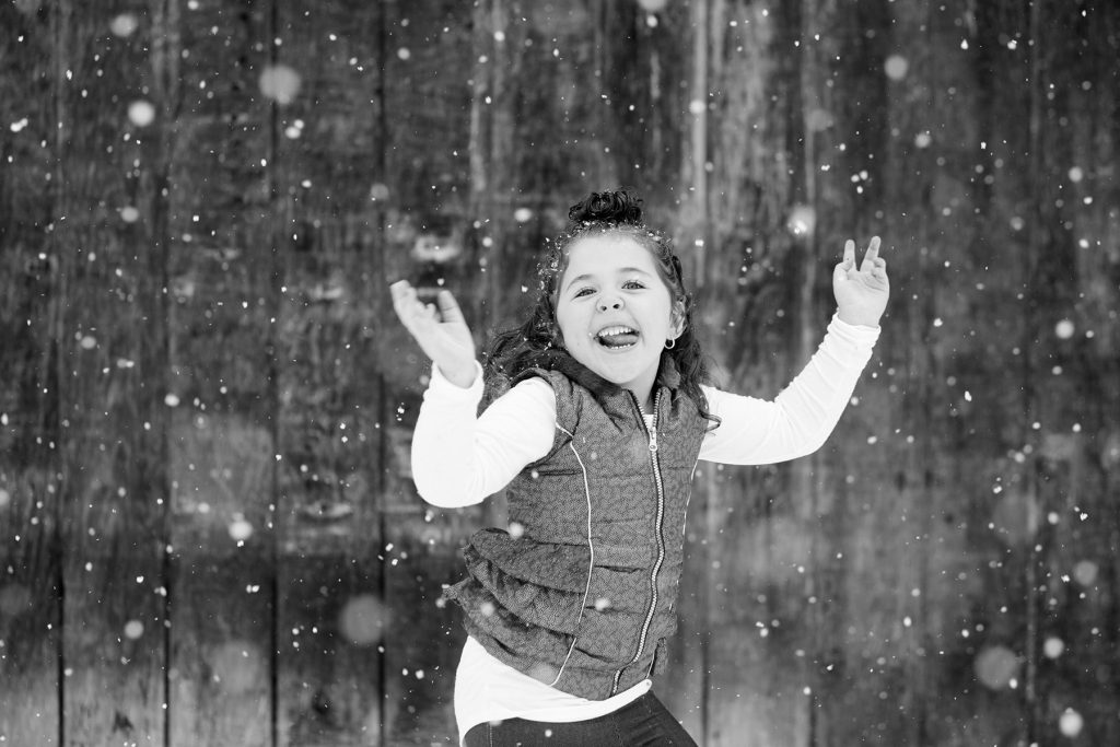 little girl dancing, during her family portrait, in the snow near Mt. Hope Cemetary in Rochester with family photography in Rochester NY